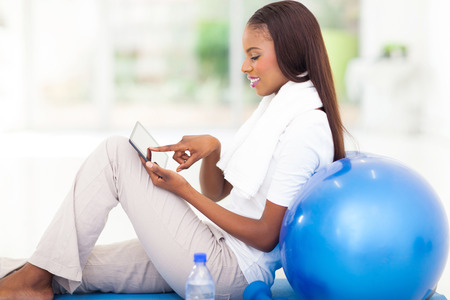 side view of young african woman using tablet computer  photo