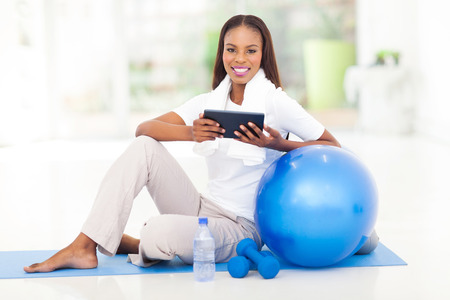 cheerful african woman holding tablet computer after exercise photo