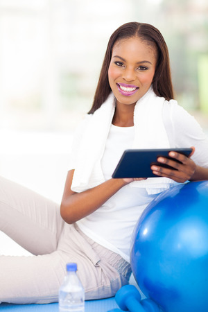 attractive young african american woman using tablet computer photo