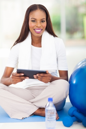 pretty african american woman holding tablet computer after workout photo