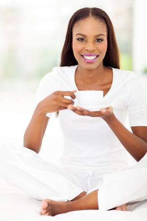 mujer tomando cafe: hermosa mujer africana disfruta de una taza de café en casa