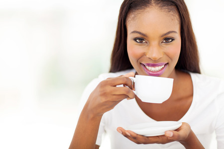 women holding cup: beautiful african american woman drinking coffee at home