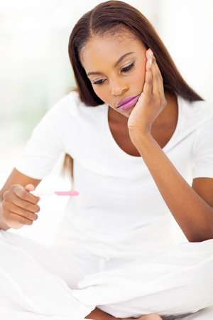sad african woman looking at pregnancy test  photo