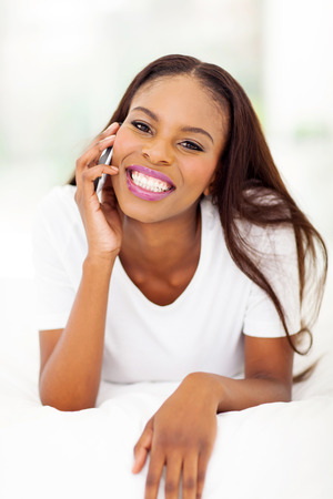 cheerful african woman making phone call in bedroom Stock Photo - 22377583