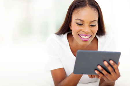 african american woman hair: beautiful black woman using tablet computer on bed