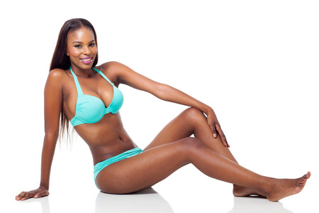 attractive african woman in bikini sitting on the floor isolated on white photo