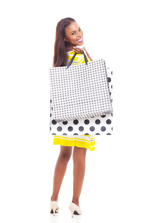 happy young african american woman holding shopping bags looking back on white background photo