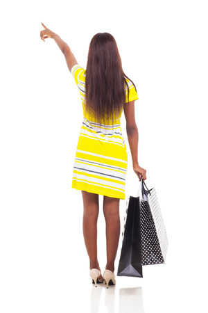 rear view of african american woman pointing with shopping bags isolated on white background photo