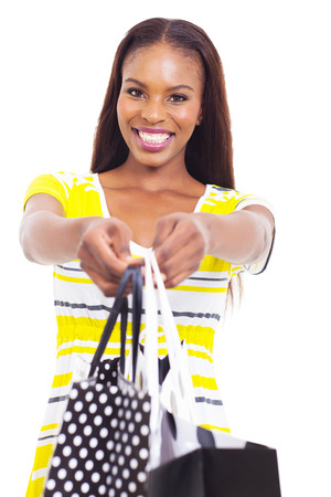 happy african american woman offering shopping bags over white background photo