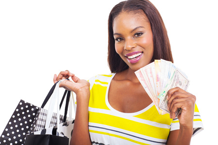beautiful african woman holding a hand full of cash and shopping bags on white background photo