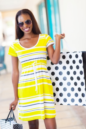 happy african woman holding shopping bags in mall photo