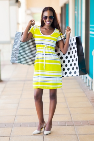 happy african woman with shopping bags in mall photo