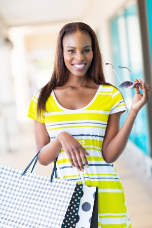 happy african girl with shopping bags in mall photo