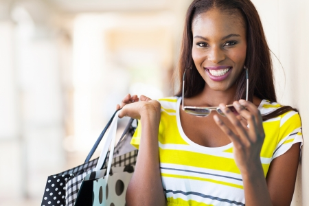 cheerful african american woman shopping in mall photo