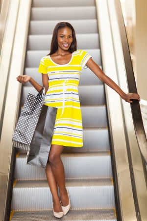 shopping african woman using escalator in shopping mall photo