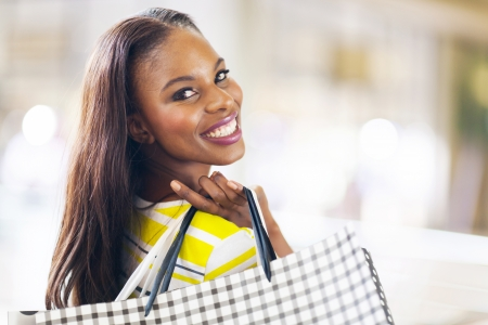 happy shopper: pretty african young lady shopping in mall