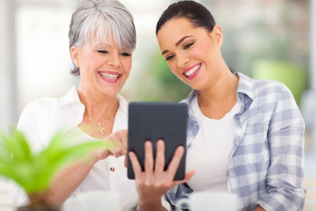 happy senior mother using tablet computer with daughter at home photo