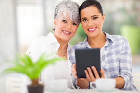 beautiful daughter using tablet pc with her middle aged mother photo