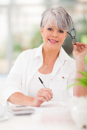 happy senior woman doing home finances photo