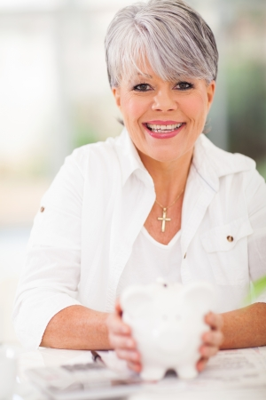 cheerful senior woman holding piggybank  photo