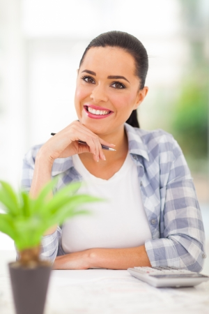 savings problems: smart young woman calculating her savings at home Stock Photo