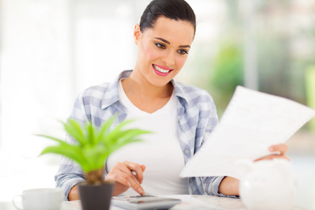 investment analysis: young woman paying her bills at home
