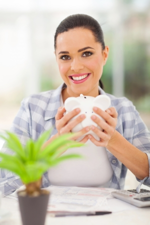 happy young woman holding piggybank and calculating savings photo