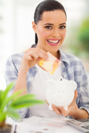 cheerful young woman putting money in piggy bank photo