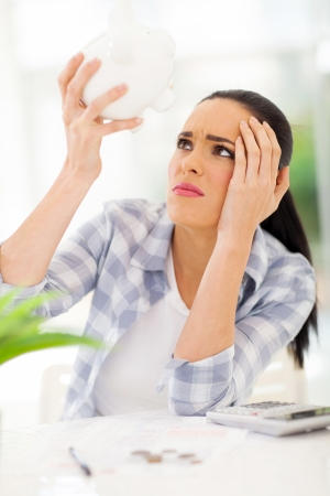 savings problems: unhappy young woman having financial problems and emptying piggybank savings to pay bills