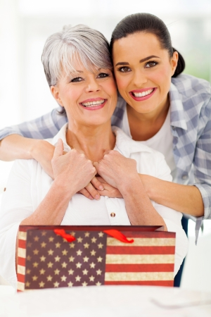 happy mature woman receiving gift from daughter on mothers day photo