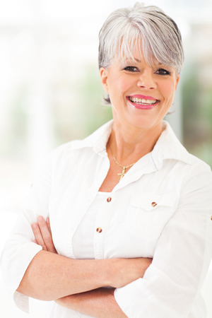 cheerful middle aged woman with arms folded photo