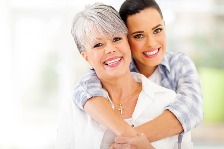 happy young woman hugging middle aged mother at home