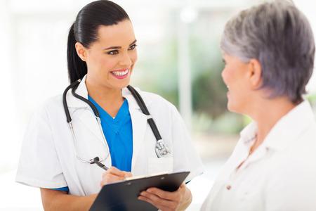Hermosa enfermera joven médico hablando con paciente senior Foto de archivo - 22404518