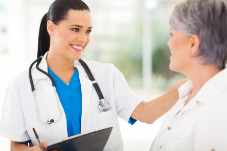 patient: friendly female doctor comforting middle aged patient in hospital