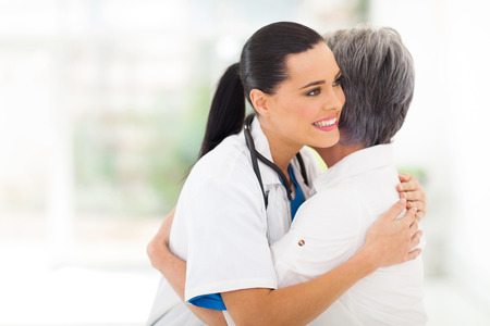 caring: caring young medical doctor hugging senior patient