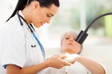La peau amicale dermatologue examine Senior femme sous la lumière Banque d'images - 22404525