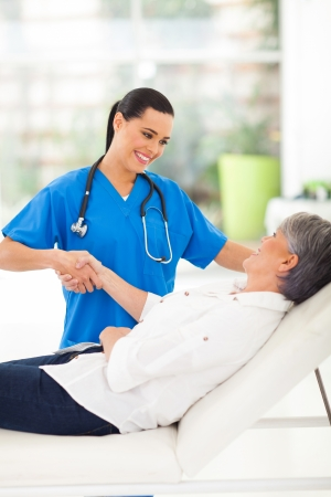 work checkup: female doctor handshaking with middle aged patient before checkup Stock Photo