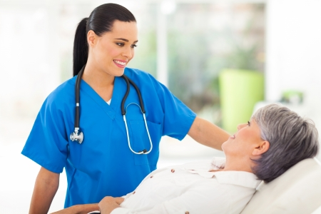 hospital patient: beautiful medical nurse talking to senior patient before checkup