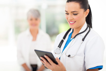 Office uniforms: hermosa trabajador de la salud femenina con tablet PC en el hospital