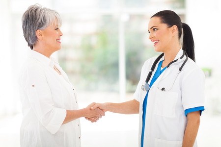 attractive medical doctor handshaking with middle aged patient