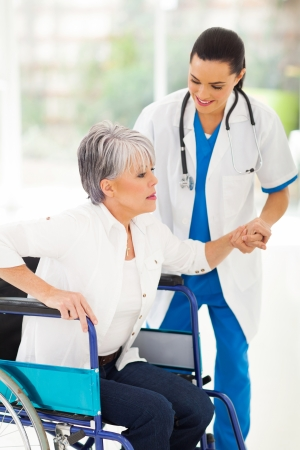 beautiful medical nurse helping senior woman on wheelchair photo