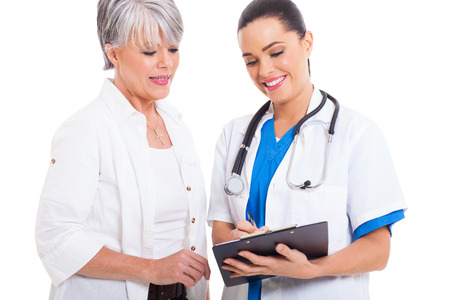 checkup: friendly doctor helping senior woman with medical form isolated on white