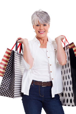beautiful senior woman with shopping bags isolated on white photo
