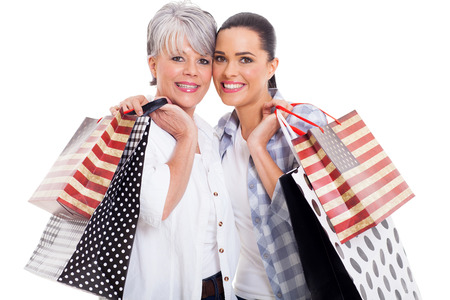 cheerful mother and adult daughter carrying shopping bags isolated on white photo