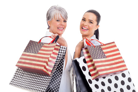 beautiful middle aged woman with her daughter shopping isolated on white background photo