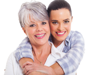 happy mature mother and adult daughter hugging on white background