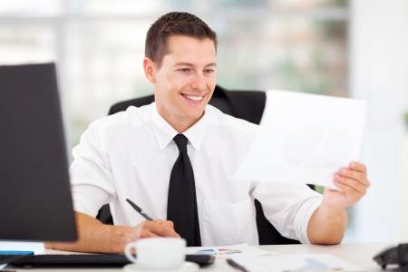 hombre escribiendo: feliz la redacci�n de informes de negocios en su oficina