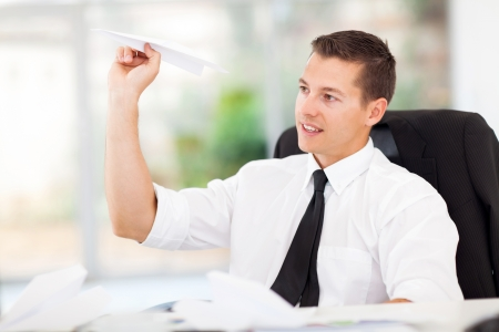 smiling businessman playing with paper airplane in office photo