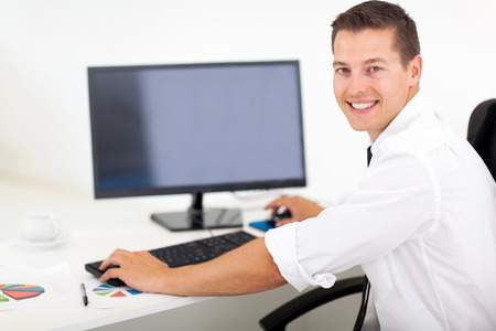 looking at computer screen: good looking businessman working on a computer in office Stock Photo