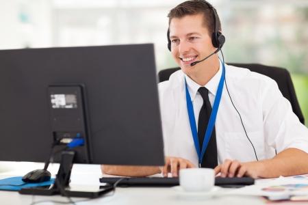 Beau opérateur de support technique travaillant sur l'ordinateur Banque d'images - 22538012